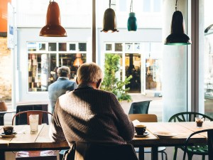 An older man sits with his back to the camera in a cafe