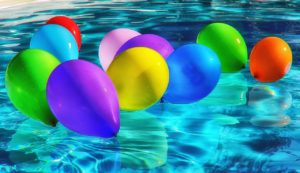 10 balloons of different colours float on the surface of a swimming pool