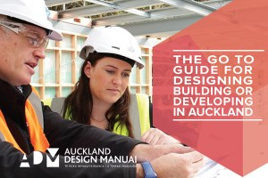 picture shows a man and woman wearing white hard hats. the white text on red background says The go to guide for designing and building and developing in Auckland