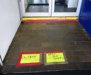 A yellow caution sign is taped to the ground with red tape. The doorway entrance has a step below the door with yellow and red tape on it.