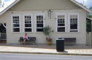 A woman sits on seat in front of a white weatherboard building. She is facing the road. There is another seat nearby and a small shrub in a pot set between the seats