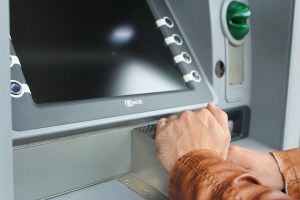 A close up of an ATM with a person holding their hand over the pin keyboard to hide their numbers