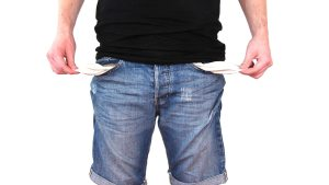 A man wearing denim shorts holds out the inners of his pockets to show they are empty.