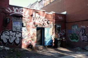 The photo shows the facade of an old red brick building with an assortment of graffiti and tags. There is a doorway and in front is a rubbish bin