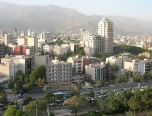 A distance view of the city of Tehran showing high rise buildings and mountains in the background