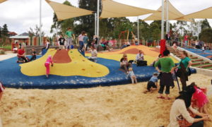 A distant picture of a playground with shade sails and sand on the ground. A large low blue platform has a yellow hump on it. Children and parents are actively playing
