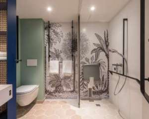Hotel bathroom with walls decorated with line drawings of palm trees and other plants. There is a shower seat, hand held shower and a toilet pan that only allows for side transfer.