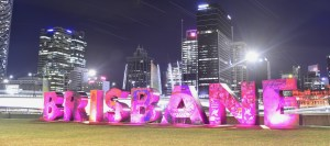 Night scene over Brisbane river with bright pink upper case lettering saying Brisbane.