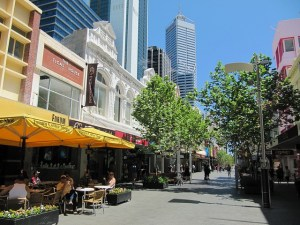 long view of a Perth city mall with shops and cafes under awnings and trees for shade. Tall buildings are in the background