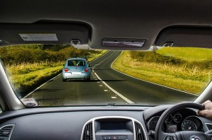 View through a car windscreen to a country road with one car in front.