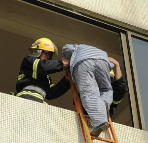 Picture taken looking up a building where a man in striped pajamas is being helped onto a ladder by two firefighters