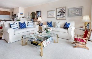 Lounge room with two white couches with blue cushions. A rocking chair with red cushions is also in the picture