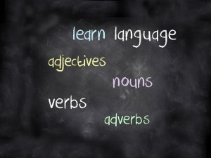 A blackboard with words: learn, language, adjectives, nouns, verbs, adverbs written in chalk