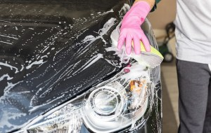 Front of a black car with soap suds and someone with a pink gloved hand is washing it