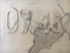 A grey marble wall has numbers embossed on it. It is difficult to see unless there is shadow on the embossing because the marbling effect disguises it.