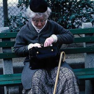 Patricia Moore sits on a park bench looking in her handbag. She has a walking cane and is wearing a black hat an blue overcoat. She looks like she is 80 years old but she is 27.