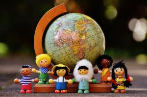 A globe atlas of the world sits on a desk and lined up in front are small dolls representing different countries