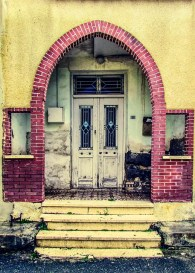 A yellow brick house with yellow steps to the front door set back under a red brick archway.