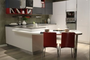 A kitchen with white cabinetry and a bar extension showing two place settings and chairs. The future of kitchens