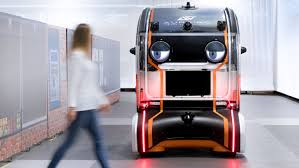 An orange automated vehicle has eyes that appear to be looking at a pedestrian