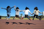 Four children are in an open space with buildings in the background. They are jumping in the air and holding hands .