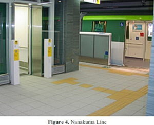 Train platform showing wheelchair crossings across a strip of yellow tactile markers.