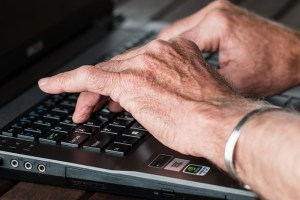 A pair of older hands are placed over the keyboard of a computer.