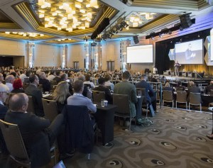 A large conference venue with a speaker on stage and a large audience.