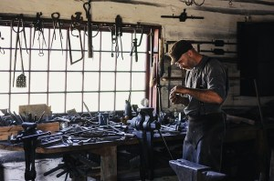 A man stands in a workshop with lots of tools around him. He is looking at something small in his hands.