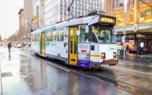A Melbourne tram moves along a quiet street after the rain. A cyclist is in the background.