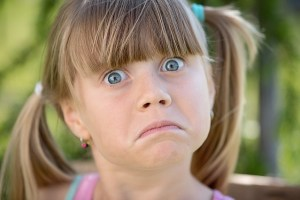 A young girl is wide-eyed with a drooping mouth as is she is about to be unhappy. Autism and building design.