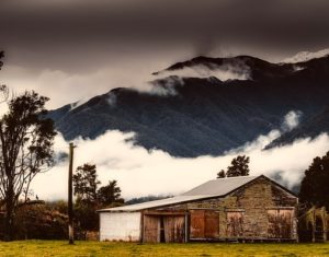 An old weatherboard farm building sits in front of a tall dark brooding mountain.