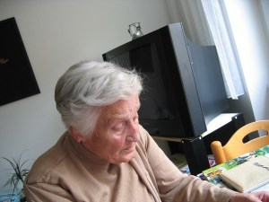 An older woman sits at a table in a room with a tv behind her.
