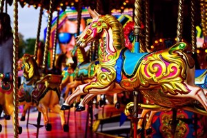 A brightly coloured horse on a carousel ride.