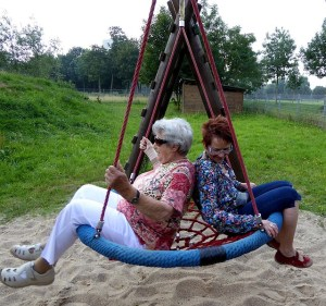 Two women sit on a bird nest swing.