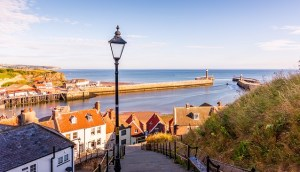 A distance view of an English coastal village showing a harbour wall.