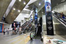 Station in Singapore showing complexity of design with escalators and shiny surfaces.