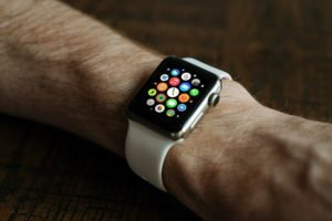 On a man's wrist is a Apple Smart Watch. The face has multiple coloured dots.