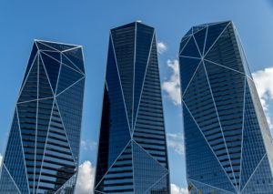 Three shiny blue apartment towers rise into the sky.