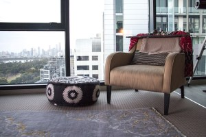 An armchair is by a big window in a high rise building. Through the window you can see the tops of other buildings in the distance.