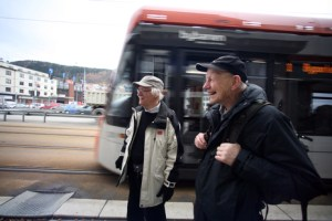 Two older men with winter jackets look happy as they stand by the train.
