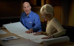 Chris Downey sits a a desk with a woman and there are tactile architectural plans on the desk in front of them.