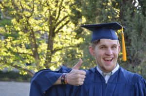 A young man in a blue academic outfit is smiling at the camera and is giving the thumbs up sign.