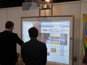 Two men in dark suits stand in front of an interactive whiteboard showing a webpage with lots of information.