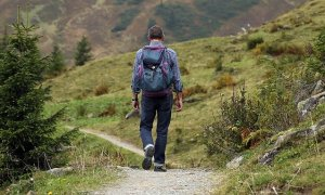 A man with a backpack is walking down a path on a hillside.