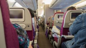 A view down the aisle of a narrow body aircraft.