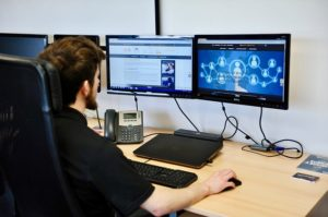 A man in a black shirt sits at a desk with two computer screens in front of him.