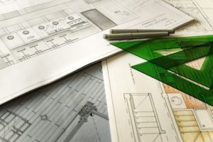A set of technical drawings with a set square and pens sit on a table top.