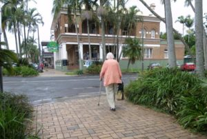 An older woman using a walking cane walks over a paved section towards the roadway.