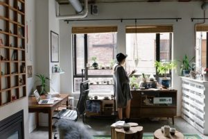 A young woman is standing looking out of the window. The room is busy with lots of things on shelves and table tops.